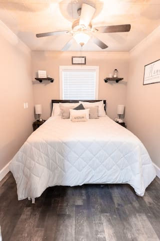Enjoy our Cozy Queen Handmade Farmhouse bed equipped with multiple pillows and 32 inch TV.