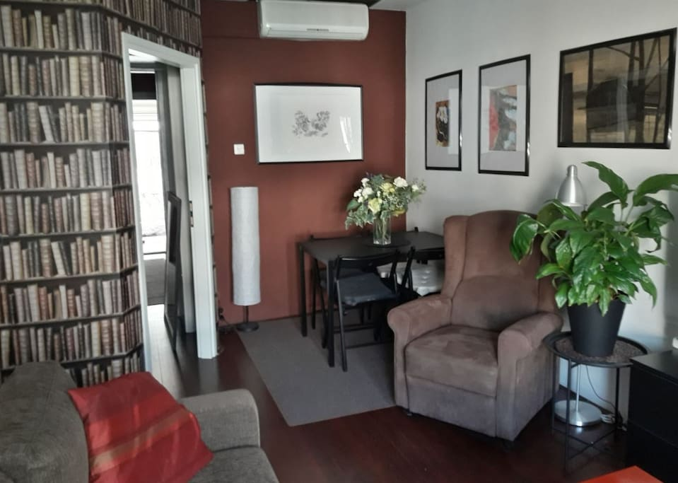 Living room with air conditioning, TV, HIFI and one sofa that can accommodate max two persons.