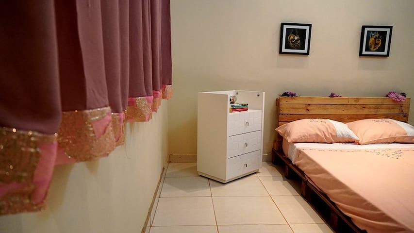 Segundo quarto com cama de casal simples, construída em pallet. Quarto com decoração em cores claras, papel de parede texturizado, criado mudo, luminárias japonesas, cômoda e guarda-roupa.