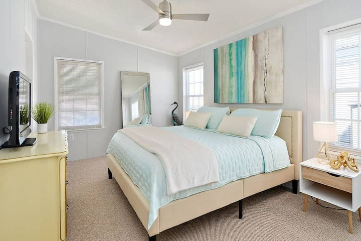 Luxurious, chic and modern master bedroom with a high quality, memory foam mattress! A remote for the light and fan! Enjoy watching the flat screen TV from the bed.