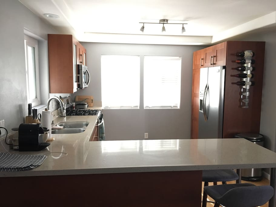 Fully stocked modern kitchen with quartz countertops and stainless steel appliances.