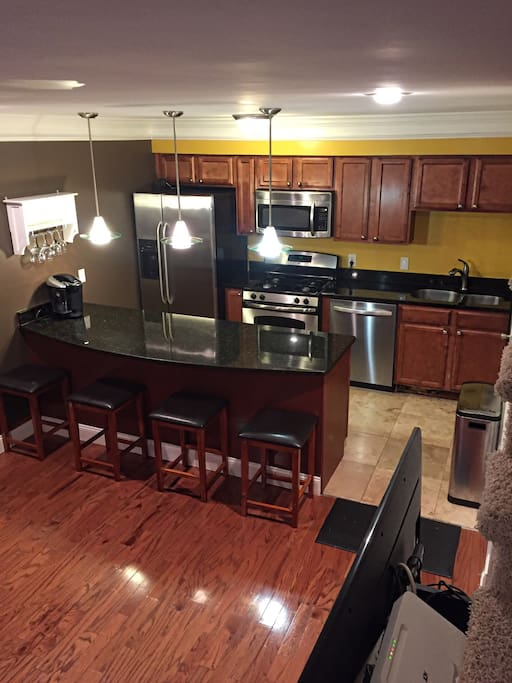Full kitchen with stainless steel appliances and a huge granite island with barstools.