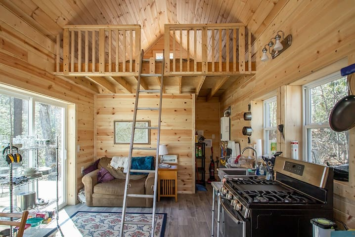 This is the interior of the red cabin showing the 6' tall sleeping loft and the kitchen area.