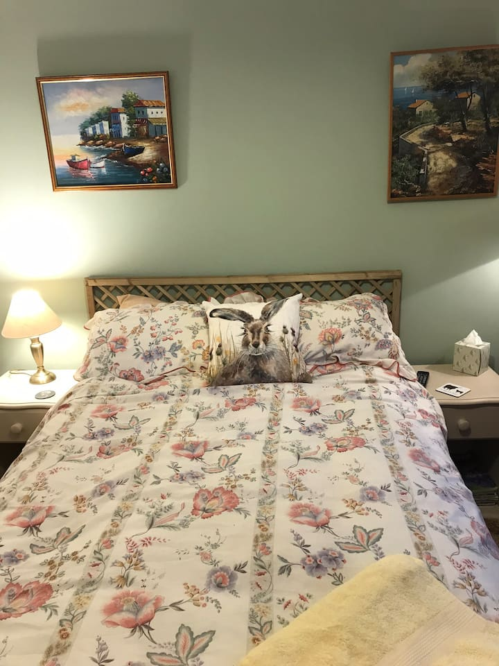 Bedroom features a small double bed and two nightstands.