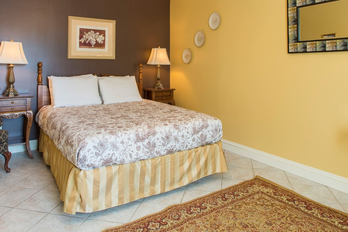Queen bed in bedroom area that is somewhat separated from the kitchen