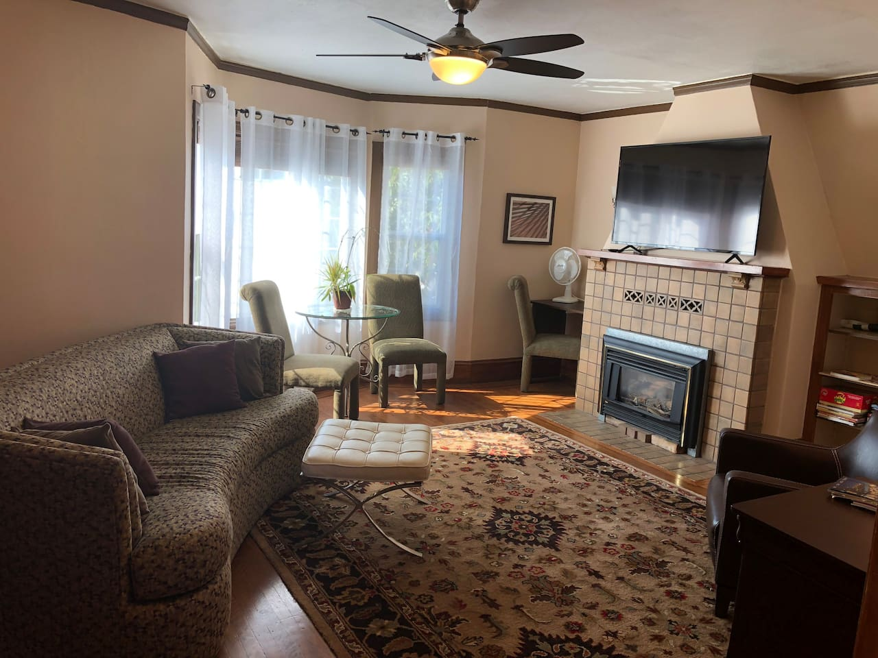 "Large living room with 55"" smart TV, dining area, board games, ceiling remote control fan."