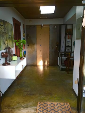 Hallway, dining area, bathroom to the left and kitchen to the right and on the other side of the sliding wall door is the bedroom.