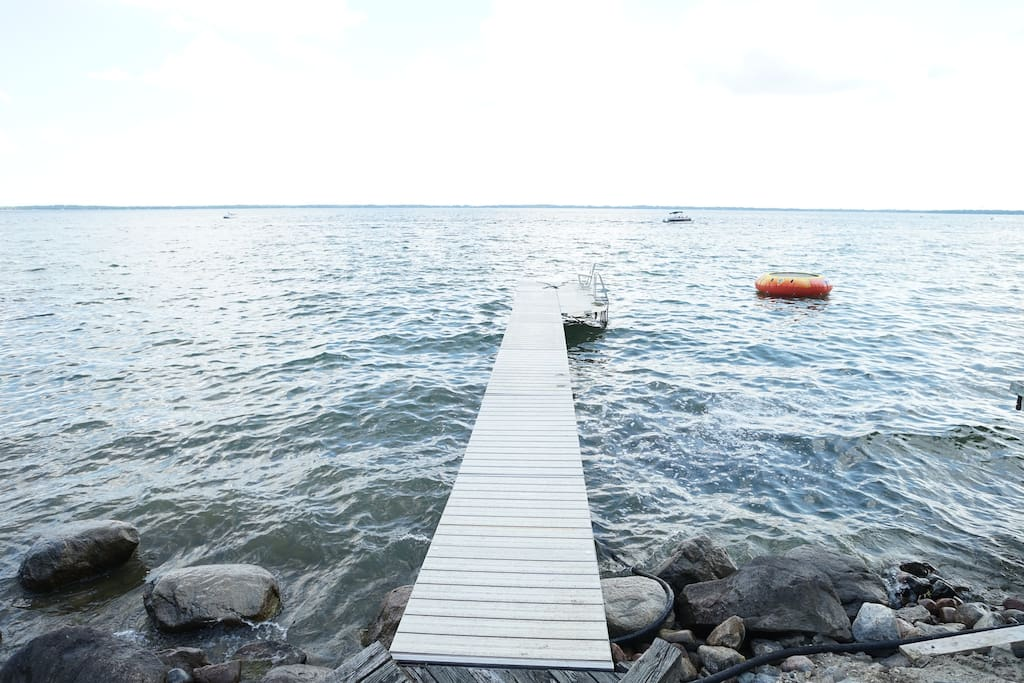 Dock, clear water and sand starting right after the rocky shoreline, water trampoline to use