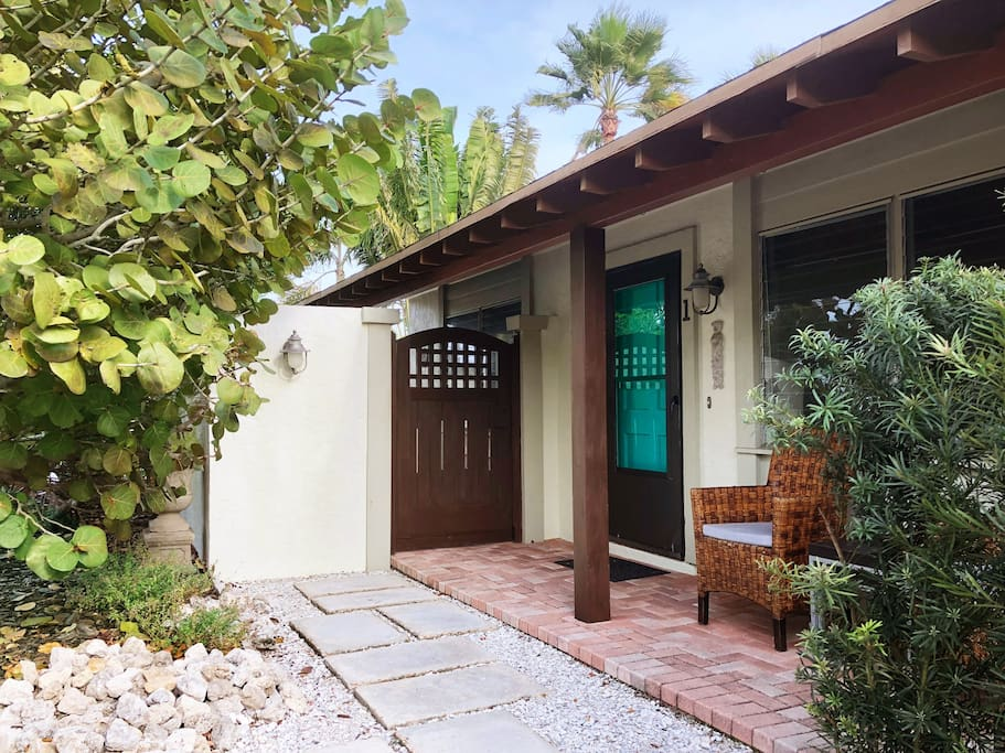 front door, covered porch, and gate to private courtyard garden
