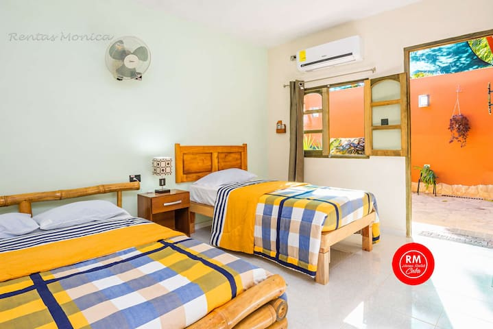 Bedroom #1 with a double bed and a single bed, air conditioning, safe for documents and money, hangers, private bathroom and minibar (beverages not included on the price).