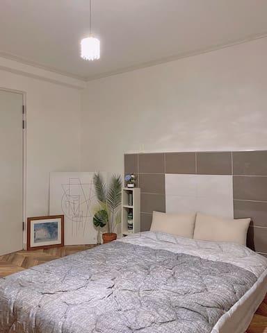 첫번쨰 침실입니다.  퀸사이즈 침대가 준비되어있습니다. 화장실이 방안에 포함되어있습니다.  창문을열면 정면의 돌계단과 나무가보이는 경관을 보실 수 있습니다.
