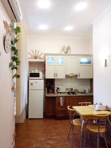 Kitchen. There is a fridge, stove, microwave, toaster, cooking utensils and tableware.