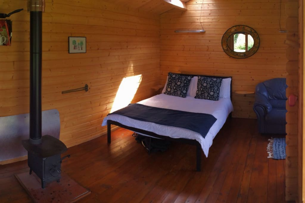 Spacious interior of one of the Huts. Full size double bed. Great wood burning stove for cooking and heating.......