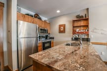 A big kitchen with granite countertops and stainless steel appliances