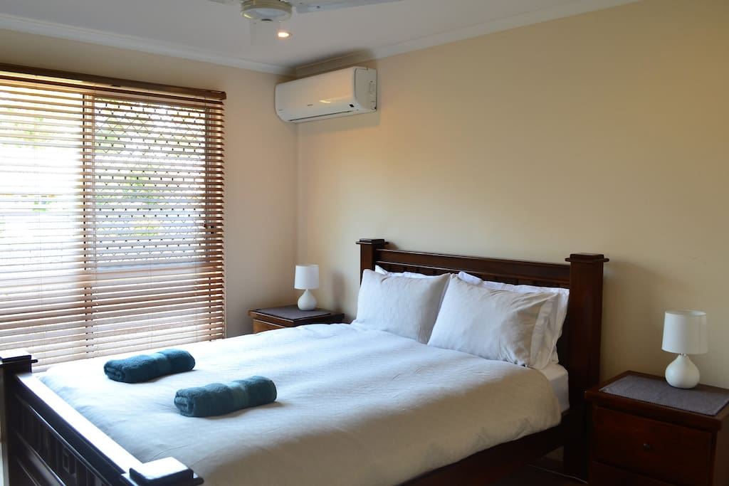 Main queen size bedroom with large walk in robe and ensuite bathroom, airconditioned and fan.