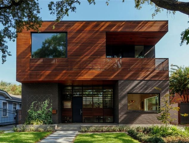 Front of home, shaded by a large live oak tree with wood paneling for privacy. Wood-panel privacy screen on second floor slides across width of house for privacy on balcony.