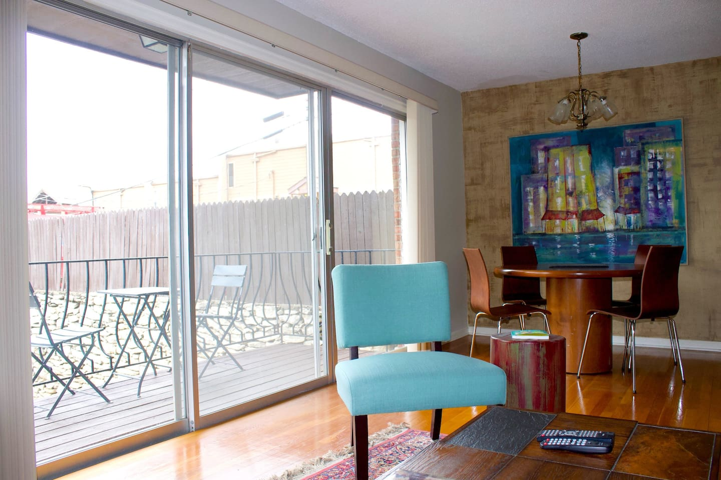 Living room opens to floor to ceiling windows and outdoor balcony overlooking courtyard.