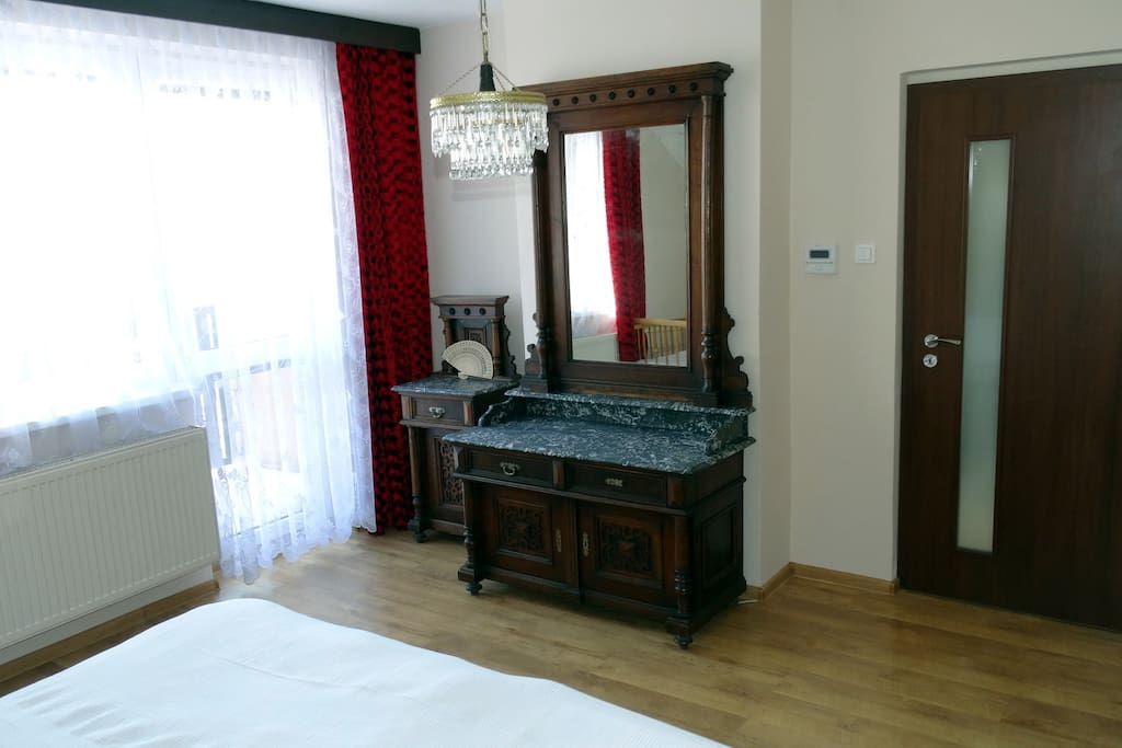 Historic mirror with marble stone top is the main feature of the master bedroom.