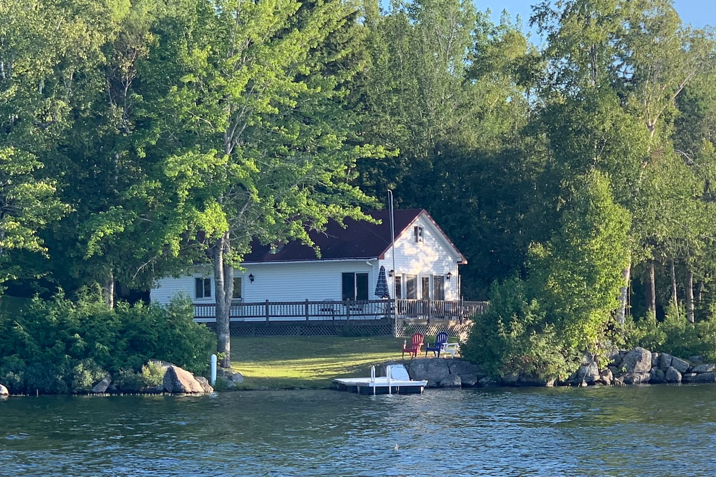Waterfront cottage (1br/1ba) with detached seasonal bunkhouse (2 sleeping rooms/ no bathroom), walk-in waterfront, dock, yard, deck, and panoramic views from the cottage's location on a small point of a crystal clear Maine lake.