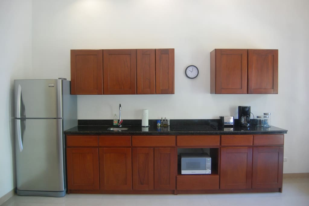 Kitchen with granit countertop, coffemaker, stove, microwave, water heater an lot more