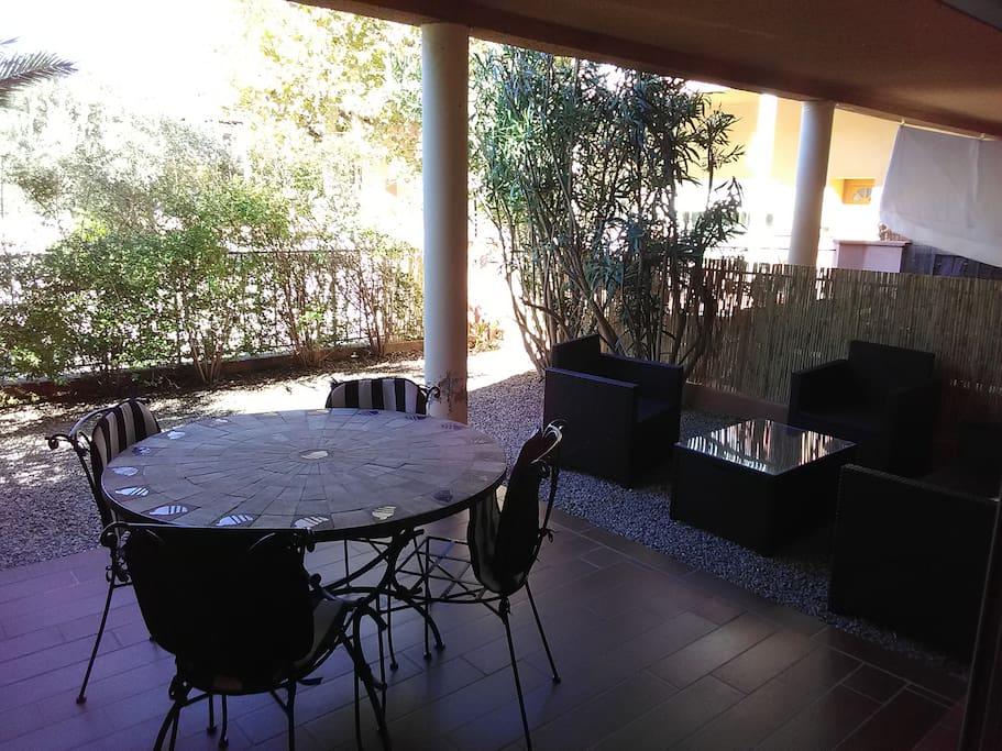 Cour arrière avec terrasse couverte et salon de jardin