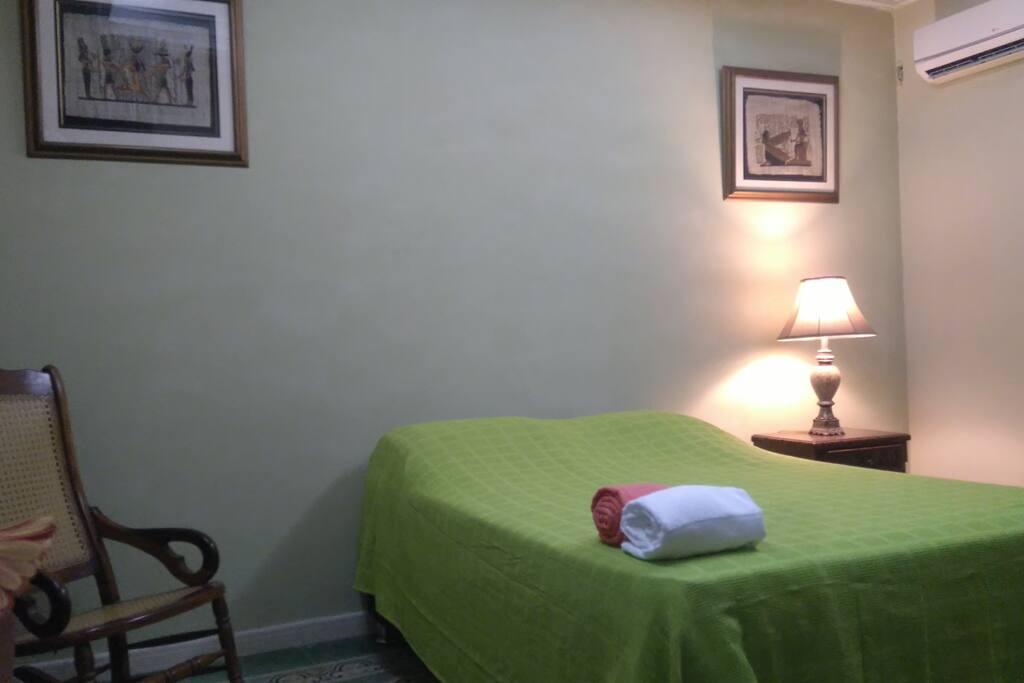 Habitación con una cama doble y una sencilla. Aire acondicionado, armario, nochero, ventilador, TV con Cable, WiFi.