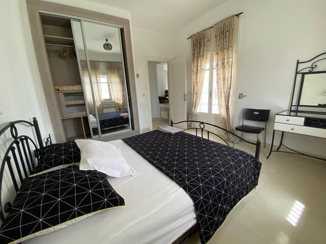 2ère Chambre à coucher au 1er étage : climatisée avec balcon, espace de rangement (placard, tables de chevet et coiffeuse) et volets roulants.