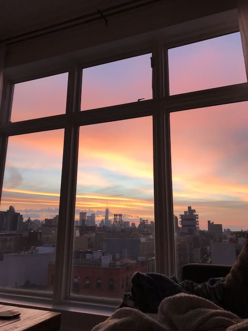 Manhattan skyline view at sunset from panoramic windows in living room.