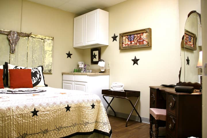 Room #7 with queen bed, sink, and vanity/stool/TV