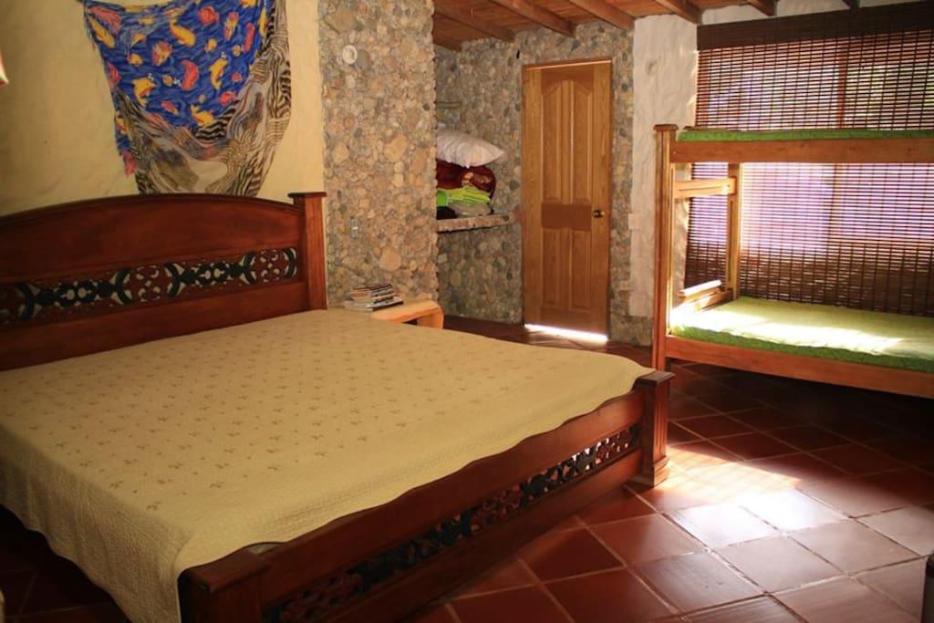 Habitación con cama matrimonial extragrande y camarote.