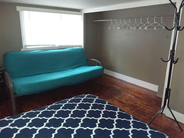 Full-size futon couch and open closet with hangers