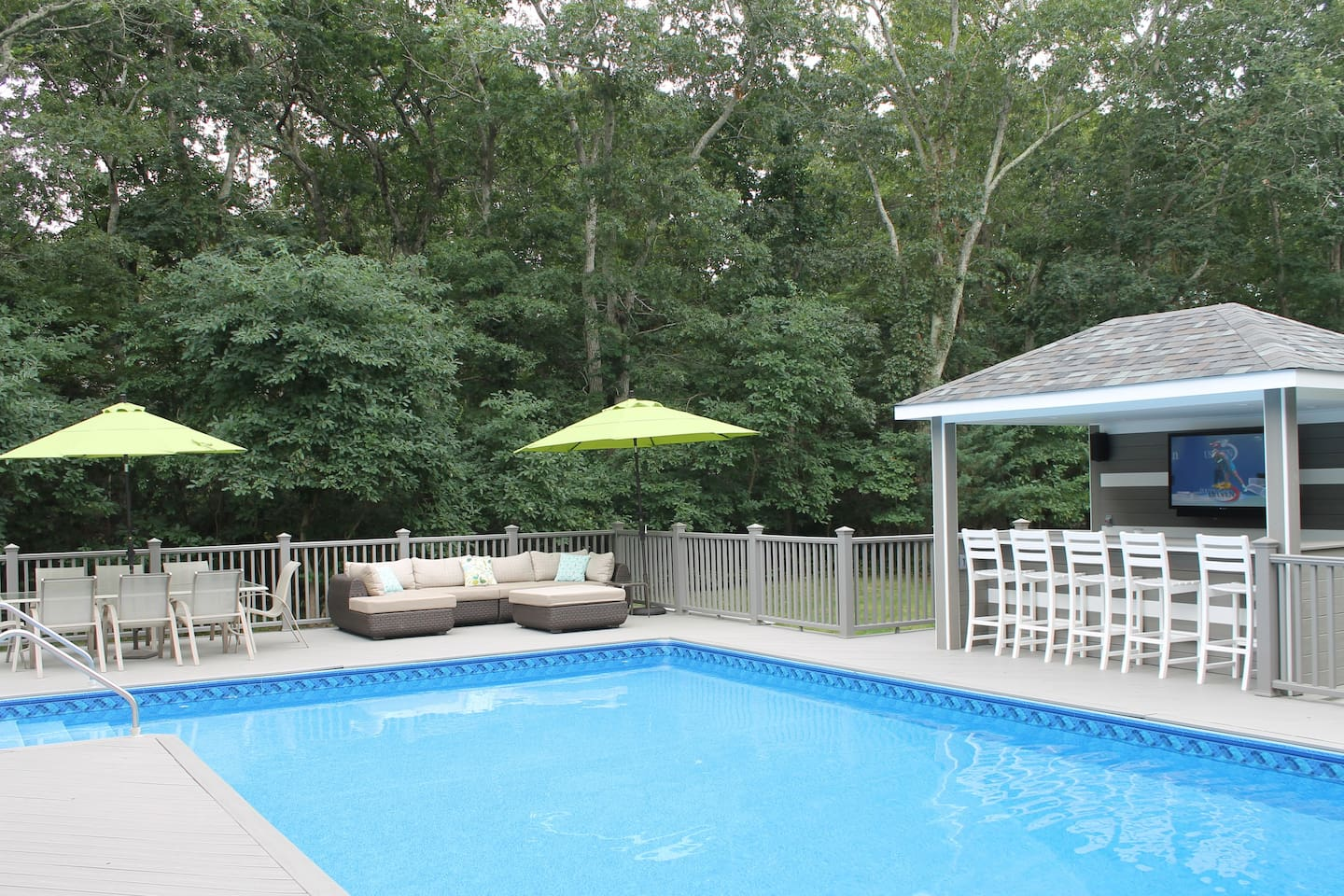 The ultra-private back deck features a heated pool, dining area, lounge area and brand-new outdoor entertainment center with a bar a TV.