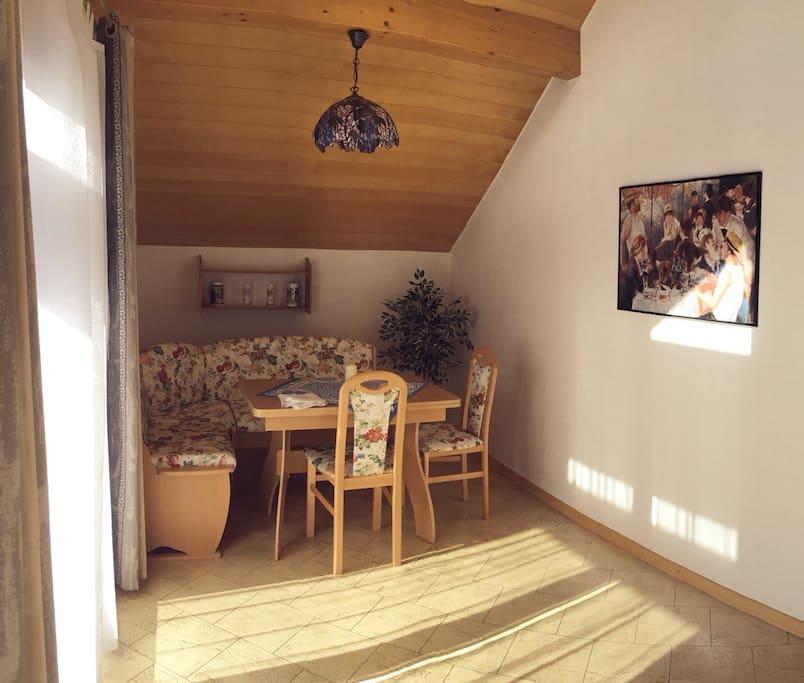 Sehr helles Zimmer mit hocher Decke, bayrische Essecke, Sofabett, TV, Stereo, Balkon  Bright and sunny living and dining room with Bavarian corner dining table, sofa bed, tv, stereo and Balcony