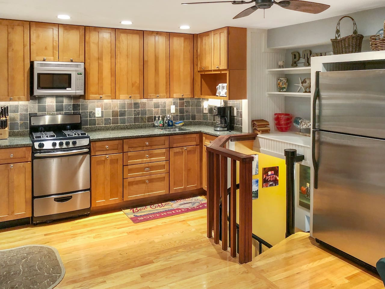 Fully stocked kitchen with stainless steel appliances, granite countertop, and slate backsplash.