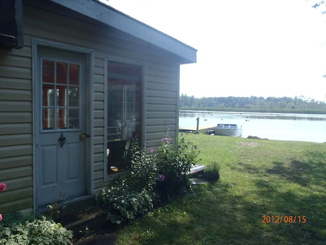 The main cottage entrance, next to a long lawn and pebbled lakefront. We have our own dock. The boat will not be available / open to the public.