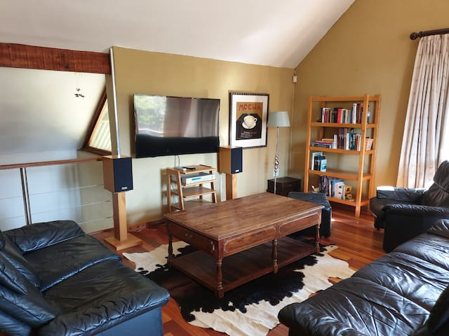 The living room has a full lounge suite with reclining chairs. The Tv has streaming content available.