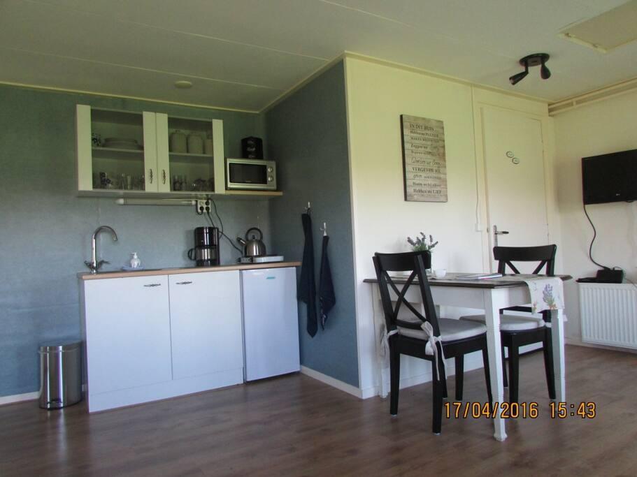De keuken met koelkast, kookplaat en koffiezetapparaat.