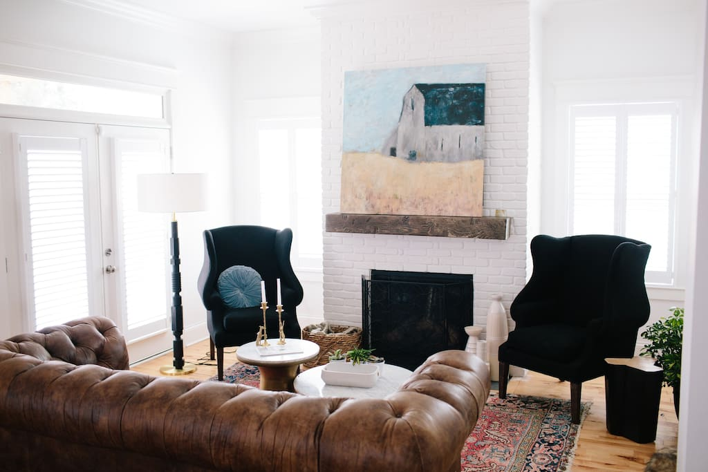 2 armchairs flank the regal fireplace