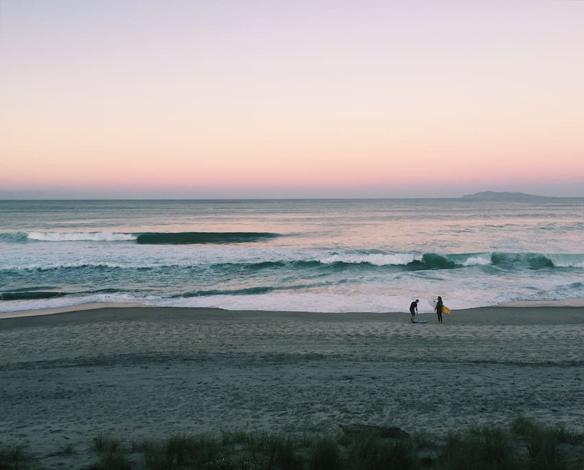 Surfers on Whiritoa Beach at dusk