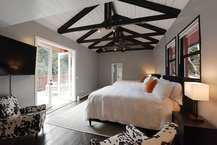 Upstairs master bedroom looks out to the canyon, trees and hills beyond.  Morning sun brightens the private deck.