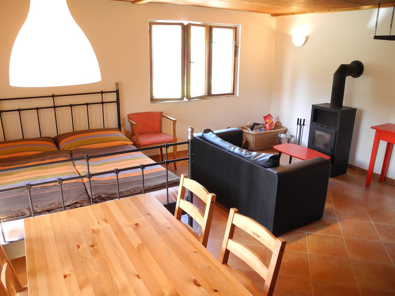Obývací pokoj s jídelním stolem, manželskou postelí a krbovými kamny připravenými k použití.