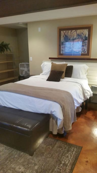 Queen size bed with quality linens and plush robes.