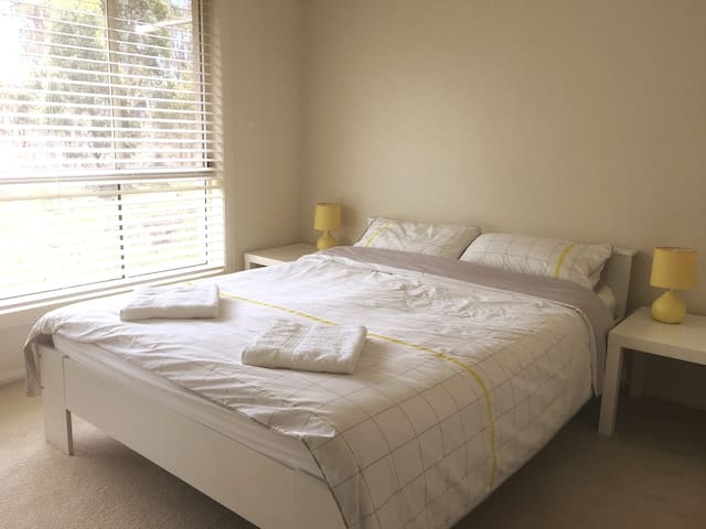 Bedroom with a queen bed and wardrobe