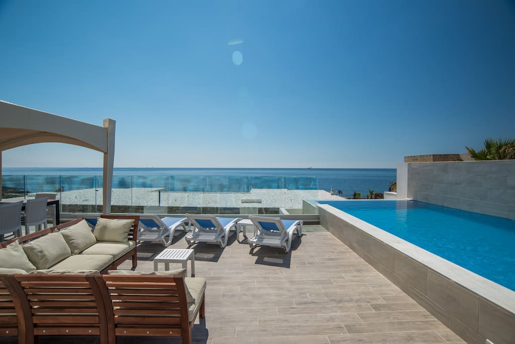 Outdoor area equipped with table, chairs, gazebo, sofa, sun loungers and barbecue