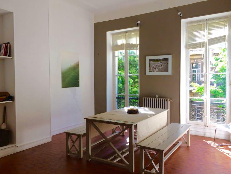 L'espace de travail et d'échange et salle à manger avec ses deux fenêtres donnant sur le boulevard Longchamp.