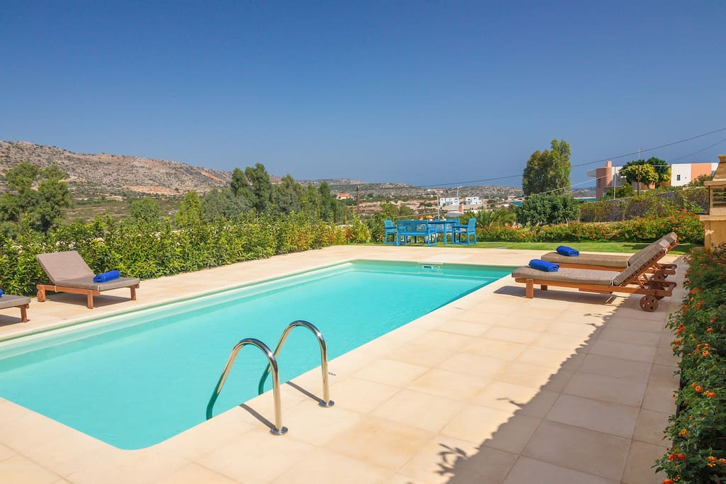 35 sqm swimming pool with sun beds and dining area
