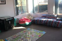 3rd living area with two single   Mattresses and toys as Well as packman PlayStation