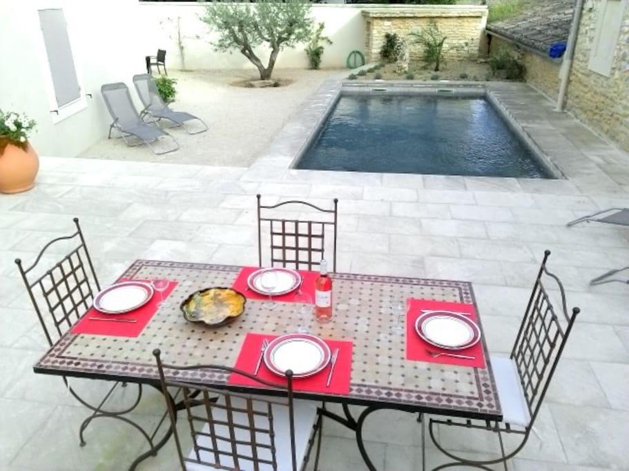 La terrasse avec vue sur la piscine et ses transats