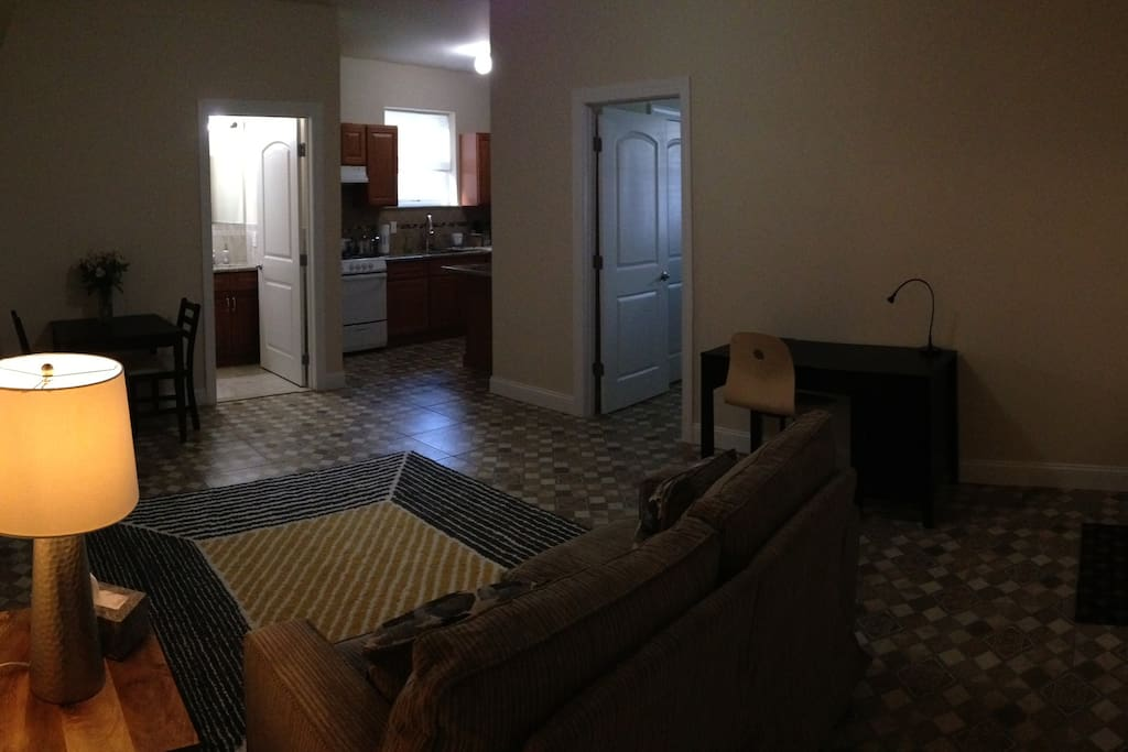 Full view of the main space. There is a desk, wheeled chair, love seat, night stand and lamp, and small dinner table on the far left side.