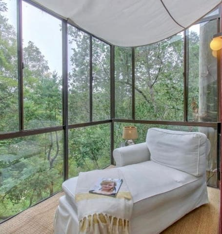 Fabulous glass enclosed sunroom on the main level perched in the treetops creates the perfect place to connect with nature.